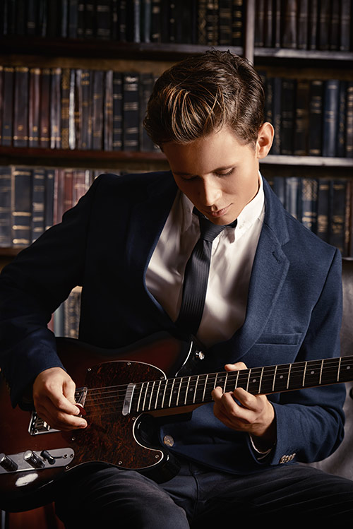 Elegant young man learning to play the guitar