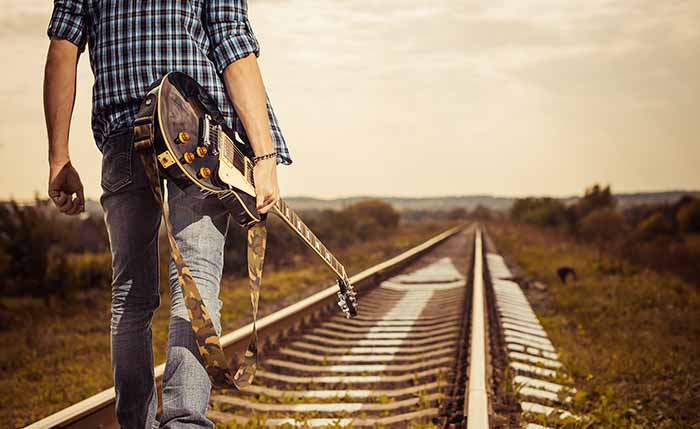 Guitarist walking next to the train track
