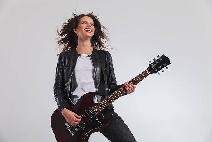 Lady smiling and enjoying her electric guitar playing
