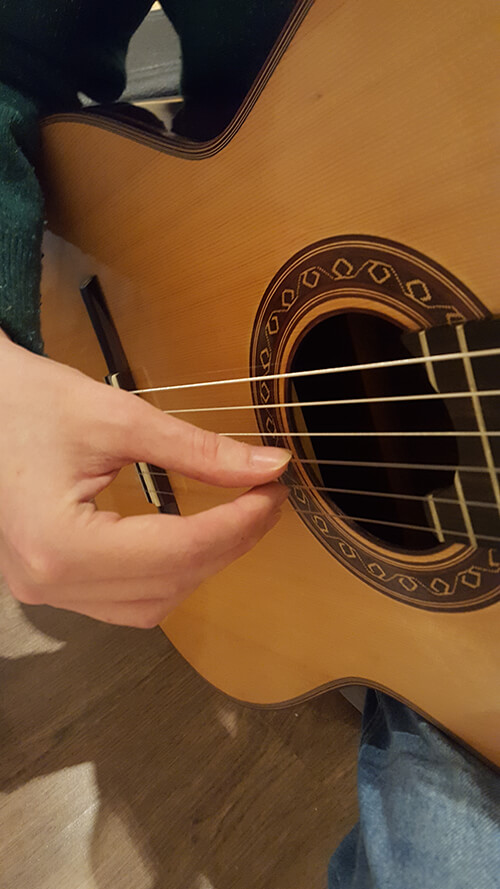 Demonstrating on the classical guitar (right hand fingers)