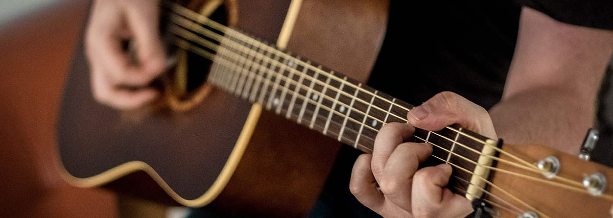 man playing the brown acoustic guitar
