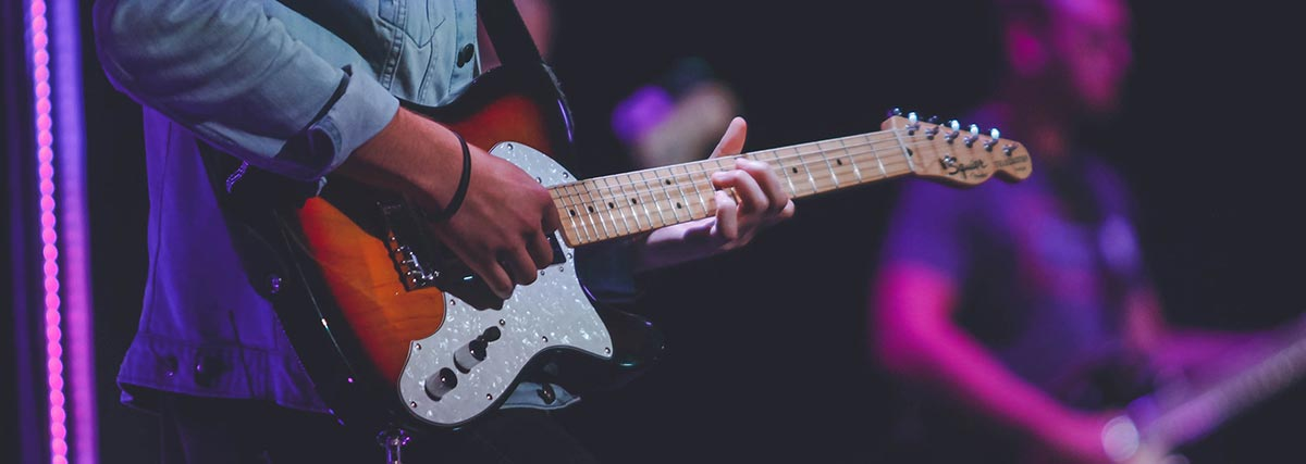 man playing the guitar on stage