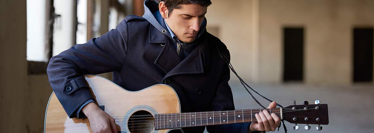 man playing the acoustic guitar