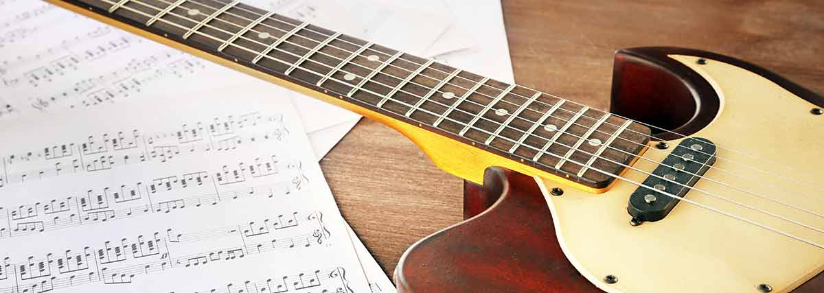 guitar-and-music-sheet-on-the-floor