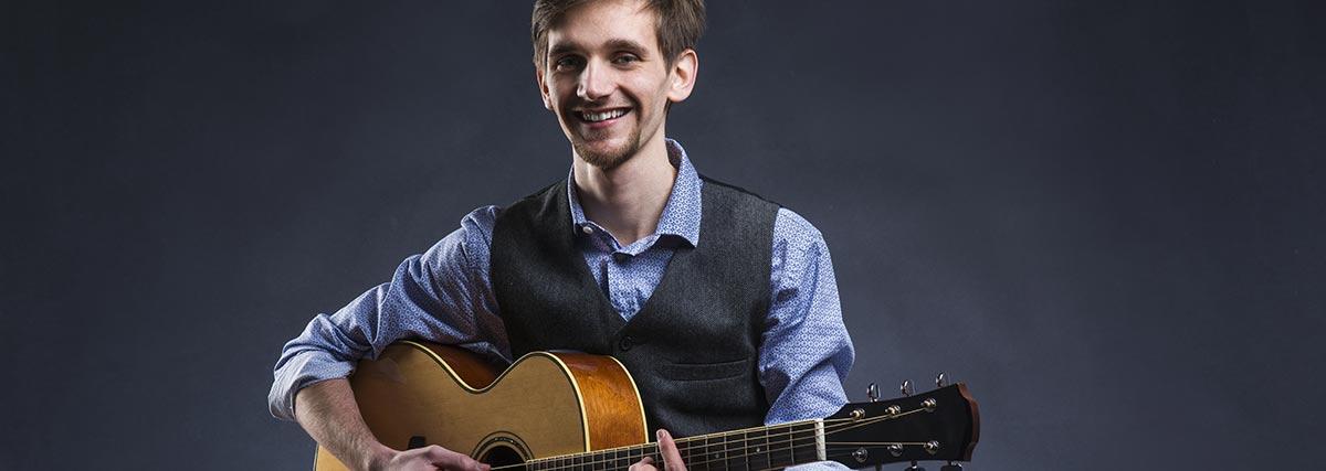 smiling-man-playing-the-guitar