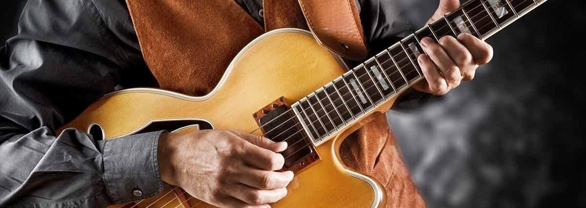 man practising the guitar