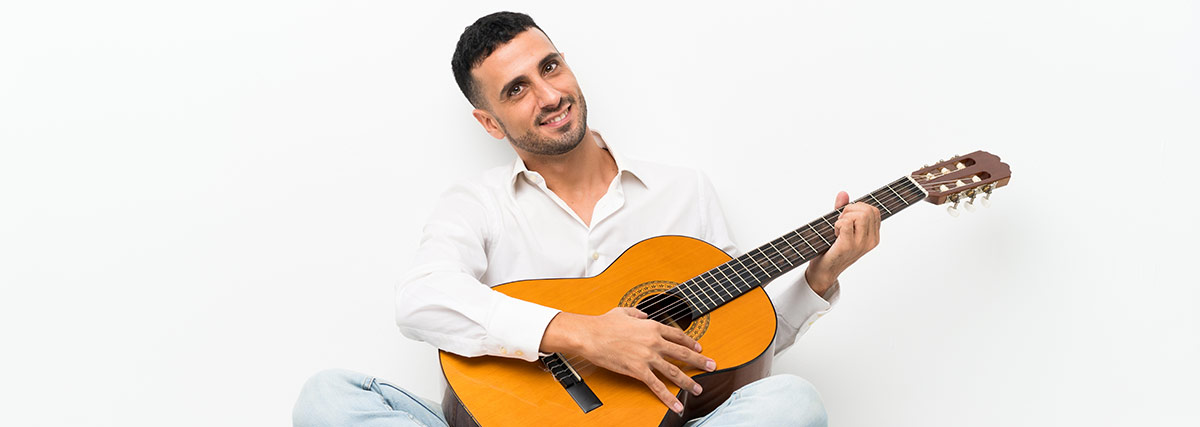 man sitting while playing the guitar