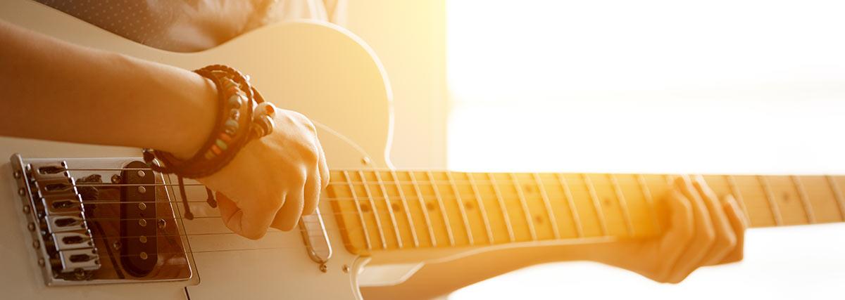 man practising the white guitar